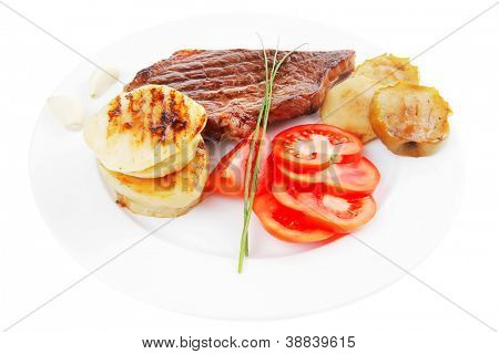meat food : roast beef fillet steak served on white plate with tomatoes , potatoes , and chives isolated over white background