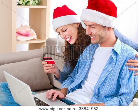 Online Christmas Shopping. Happy Smiling Couple Using Credit Card to Internet Shop. Young couple with laptop and credit card buying online. Christmas and New Year Gifts. e-shopping