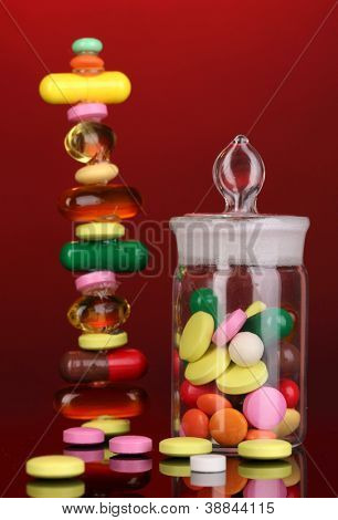 Capsules and pills hill and in receptacle on red background