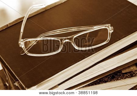 a pile of books and glasses symbolizing the concept of reading habit or studying