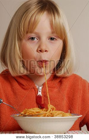 Funny young girl eating pasta.