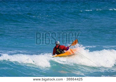 Man in a white water single kayak wearing a dry top and helmet as he rides the wave in open sea using his paddle to control his direction.