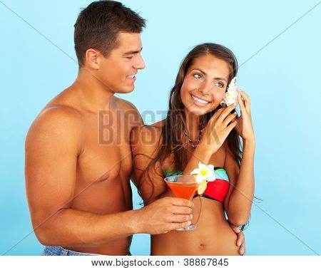 Portrait of cute girl with seashell and handsome man holding cocktail near by