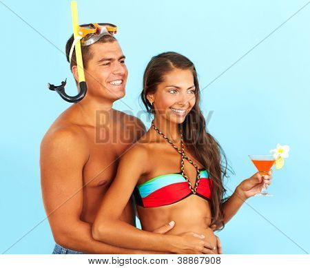 Portrait of cute girl holding cocktail with handsome man in scuba mask near by