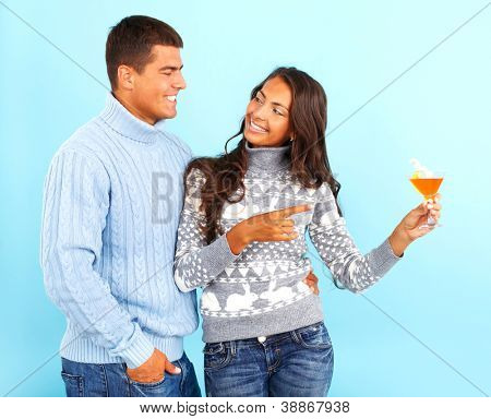 Portrait of happy girl in pullover holding cocktail and pointing at it while looking at her boyfriend