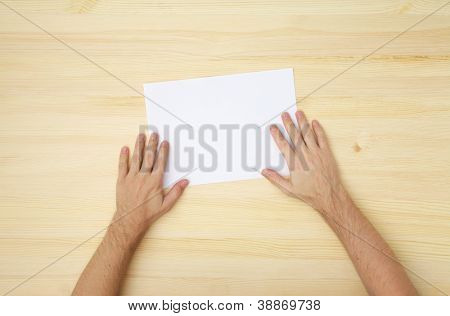 male's hand holds a blank paper