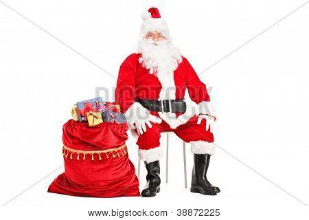 Santa Claus sentado con la bolsa llena de presenta aislado sobre fondo blanco