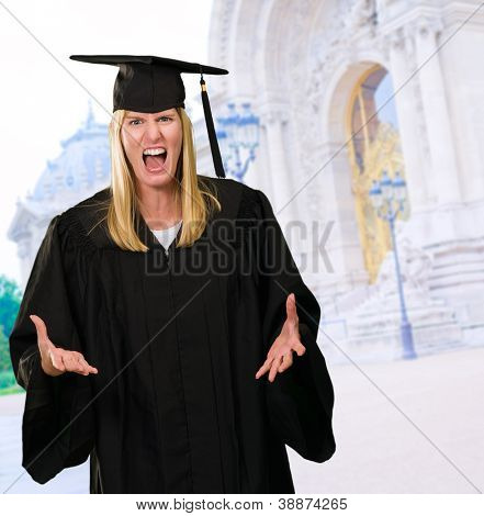 Angry Graduate Woman in front of an old building, outdoor