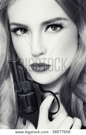 Close-up duotone portrait of young beautiful woman with revolver in her hand