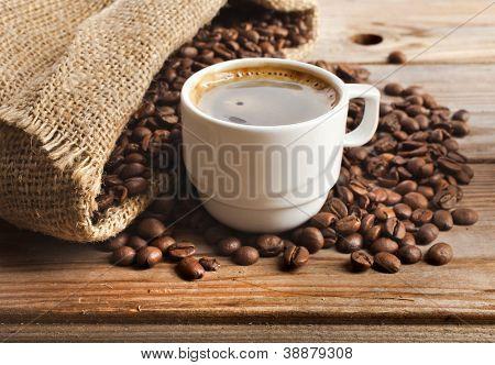 taza de café y yute saco close-up sobre fondo de mesa de madera