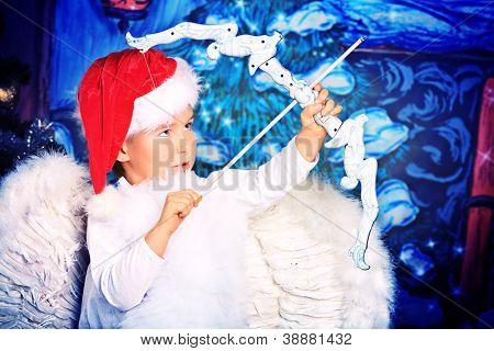 Beautiful little angel boy over Christmas background.