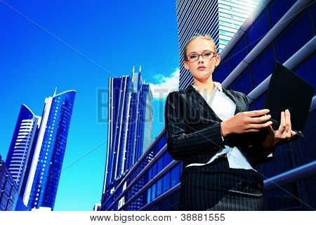 Young business woman standing with laptop in the big city.
