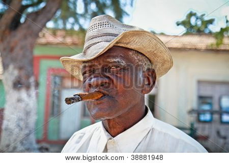 TRINIDAD,CUBA - JAN.13:Cuban man smokes a cigar on January 13, 2010 in Trinidad,Cuba. Cubans of all ages are actively smoking cigars. All the production in Cuba is controlled by the Cuban government