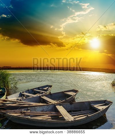 boats on water under sunset