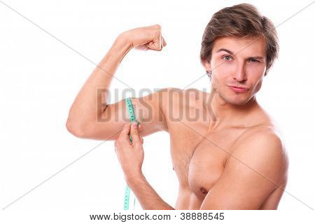 Close up of naked torso man measuring his muscle over a white background