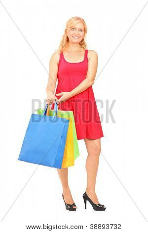 Full length portrait of a smiling mature woman holding shopping bags isolated on white background