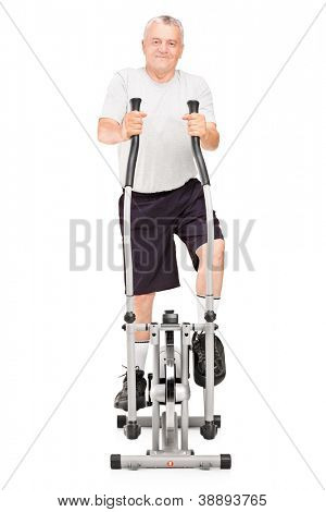 Full length portrait of a mature man excersing on a cross trainer isolated on white background