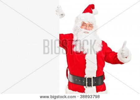 A happy Santa claus standing next to a blank billboard and giving a thumb up