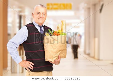 Gentelman in a shopping mall holding a bag with groceries