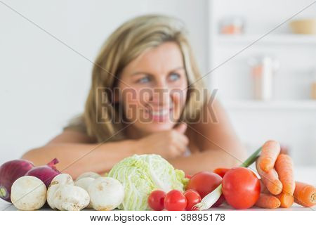 Smiling woman standing behing fresh vegetables in the kitchen