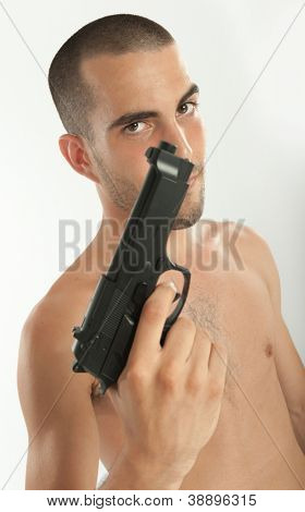 Bare-chested man holding a gun