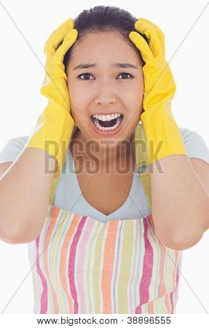 Stressed woman wearing rubber gloves and apron with her hands on head and screaming