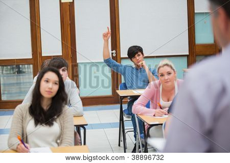 Student raising hand to ask question in college classroom