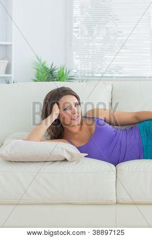 Calm brunette lying on sofa in the living room