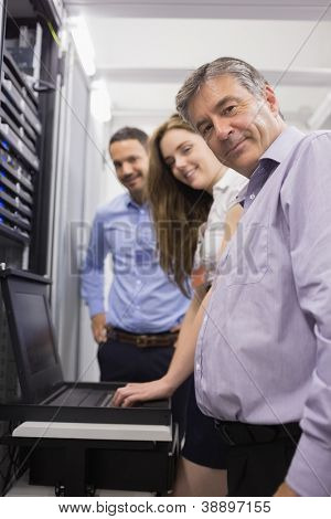 Three happy technicians checking servers with laptop in data center