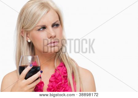 Serious blonde holding a glass of wine against white background