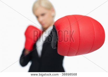 Blonde businesswoman with red boxing gloves fighting against white background