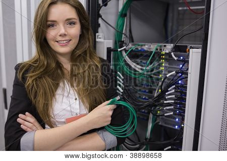 Girl holding cable in front of rack mounted servers in data storage facility