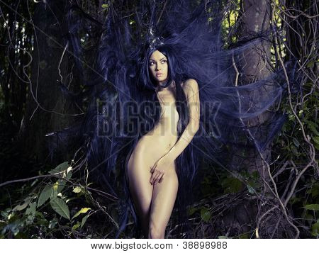 Beautiful nude lady with magnificent hair in a tropical forest