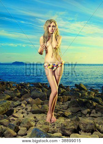 Gorgeous blonde in a flower bikini on the shore blue sea