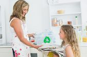 pic of take responsibility  - Mother taking newspaper from daughter for recycling - JPG