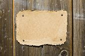 Picture of torn cardboard on wooden wall. Ready for your message. Tags and labels series.