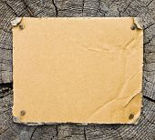 Picture of torn cardboard on wooden background. Tags and labels series.