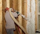 stock photo of insulator  - Worker blowing in fiberglass insulation in a house under construction - JPG