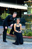 image of night gown  - Teen couple sit outdoors at a water fountain dressed and ready for prom night. Tux and gown both in black.   ** Note: Slight blurriness, best at smaller sizes - JPG