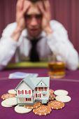 Постер, плакат: Человек рискуя его дом на игры в покер в casio