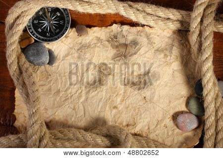 papel viejo, brújula y cuerda en una mesa de madera