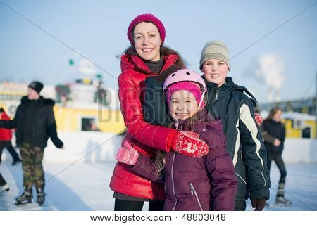 A mother with two children standing on the outdoor skating rink in winter