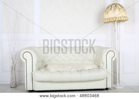 White leather sofa in room with floor lamp and white wallpapers.