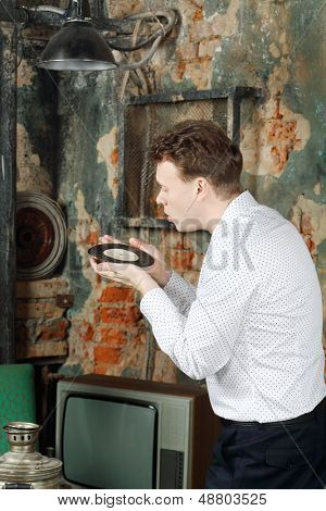 Man in white shirt blows dust off old record in very old house.