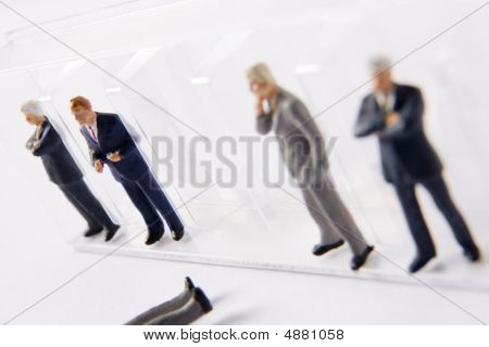 Row Of Businessman Figurines, With One Fallen Out Of Line