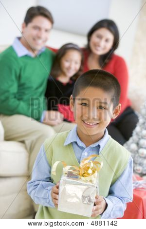 Young Boy Standing Holding Christmas Present