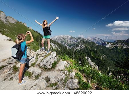 Young ladies with backpacks taking a pictures with Alps on the background