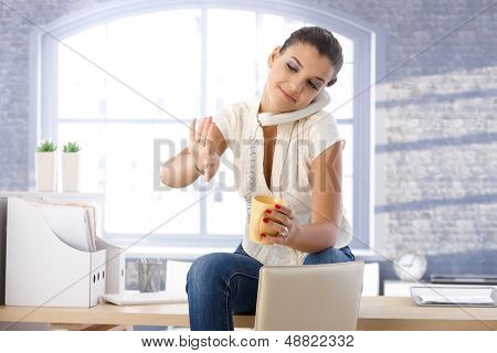 Young girl sitting in office, talking on landline phone, looking at nails, drinking tea.