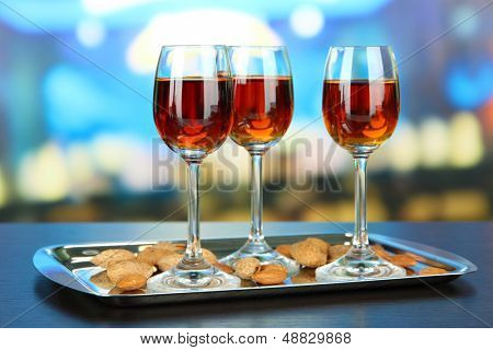 Glasses of amaretto liquor and roasted almonds, on tray, on bright background