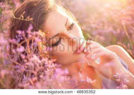 Beauty Girl Portrait. Sensual Woman Lying on a Meadow with Violet Flowers. Beautiful Woman Enjoing Nature